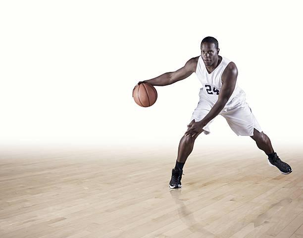 Basketball Player dribbling on a hardwood court stock photo