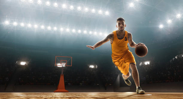 Basketball player dribbling Young muscular basketball player with a ball on floodlight professional court with a ball. Dribble jump shot stock pictures, royalty-free photos & images
