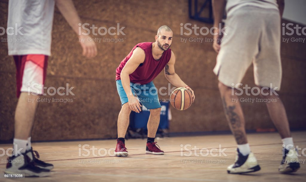 Young basketball player dribbling his opponents during the match.