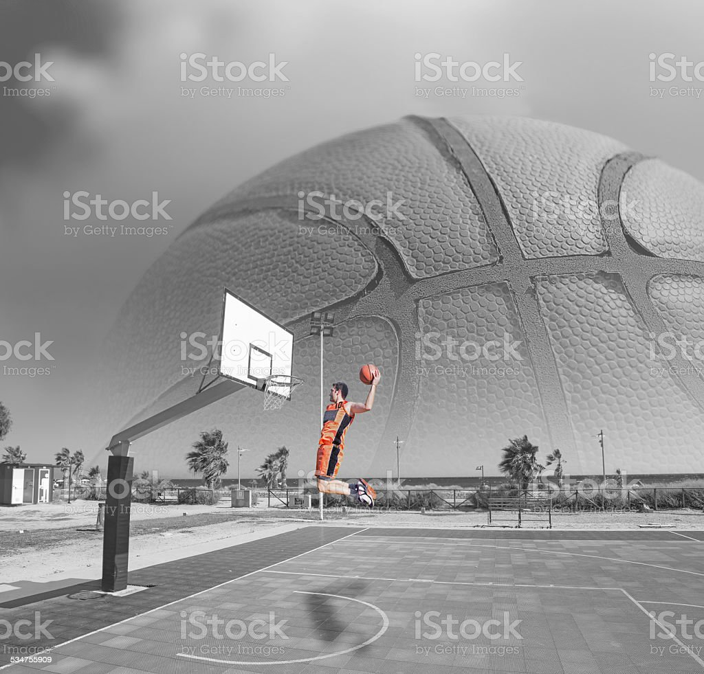 basketball player dunking by the sea stock photo