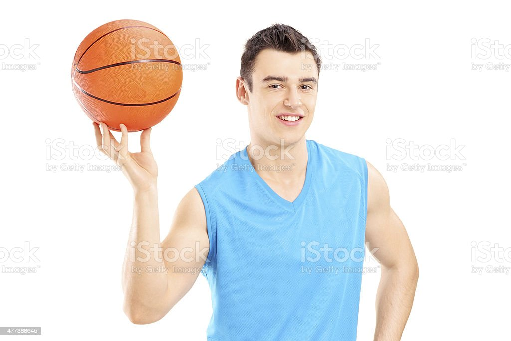 Basketball player holding a basketball and posing isolated on white...