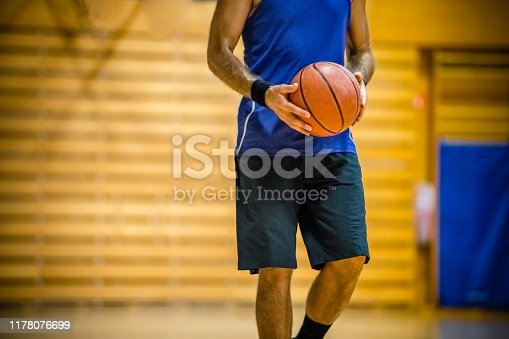 Basketball player with sports ball indoors in the Gym.