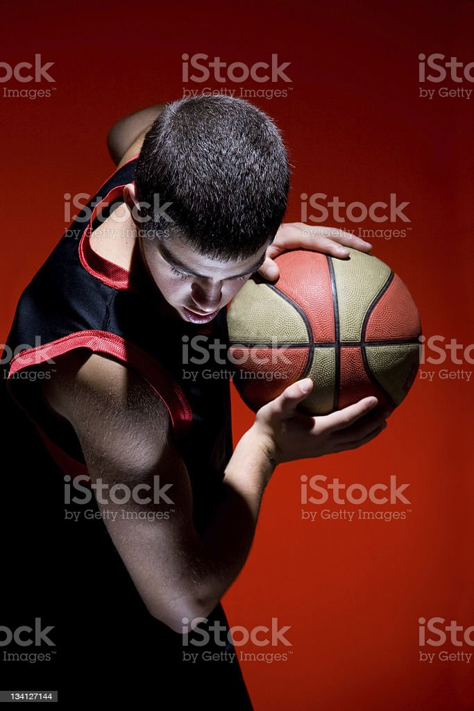 Basketball player holding ball isolated on red background royalty-free stock photo