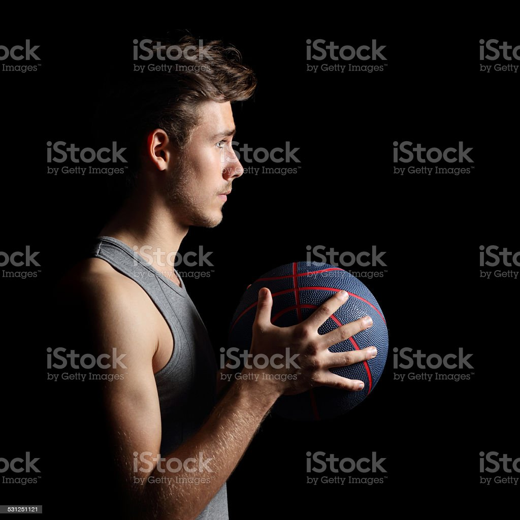 Side view of a basketball player holding a basket ball isolated on a...