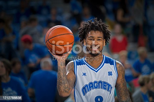 Portrait of smiling basketball player with ball standing in court at Arena Stozice, Ljubljana, Slovenia.