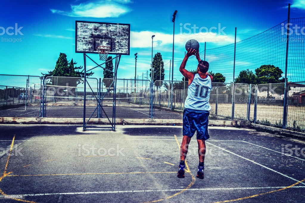 Basketball player in a playground stock photo