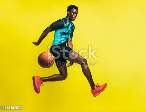 Young basketball player dribbling a ball over yellow background. Man in sportswear practicing basketball.