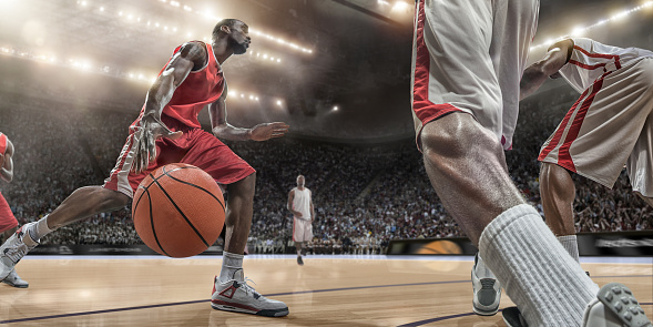A close up image from a low angle viewpoint of a basketball player dribbling basketball in front of rival players, in mid action. The action takes place in generic indoor floodlit basketball arena full of spectators. All players are wearing generic unbranded basketball kit, and all stadium advertising is fake.