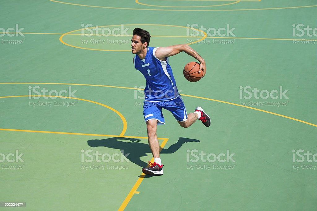 Basketball player in dribbling action stock photo
