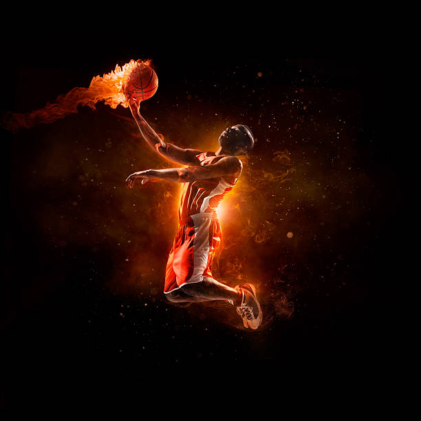 Basketball player in jump shot with fireball Close up image of professional basketball player about to do slam dunk fireball during basketball game in floodlight jump shot stock pictures, royalty-free photos & images