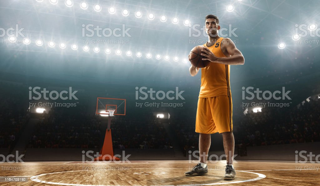 Young muscular basketball player with a ball on a floodlit basketball...