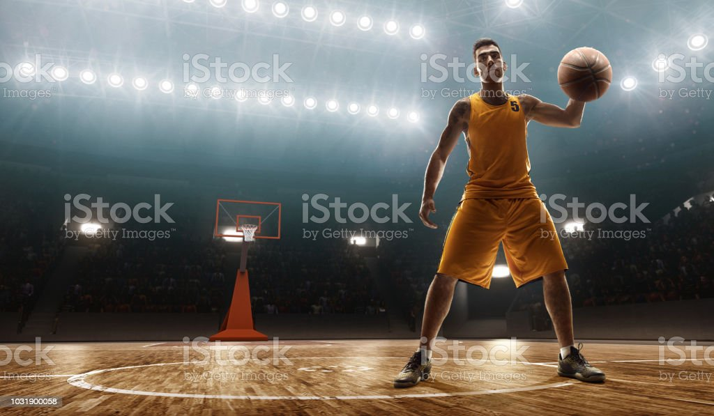 Young muscular basketball player with a ball on floodlight...