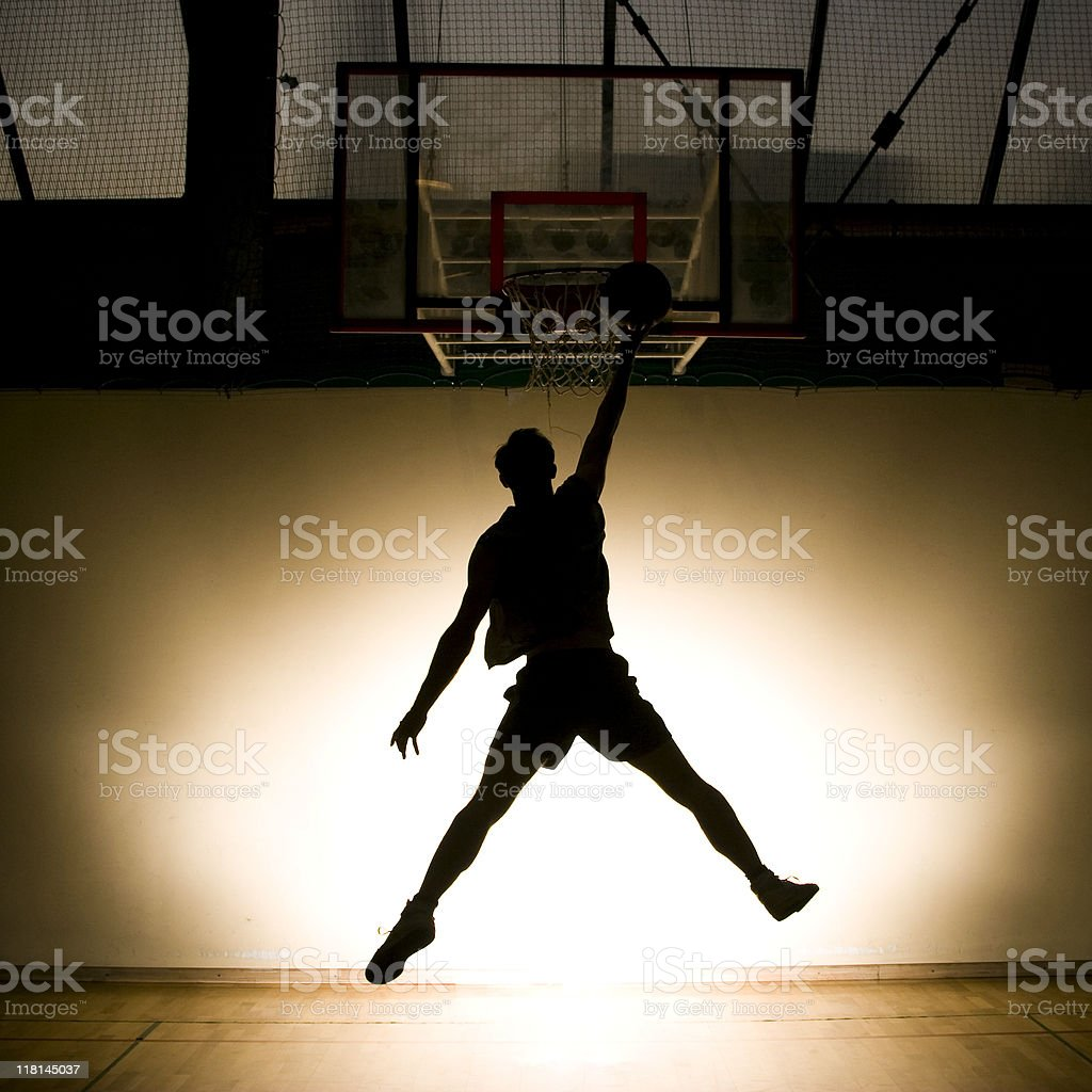 Basketball player jumping with ball, backlit royalty-free stock photo