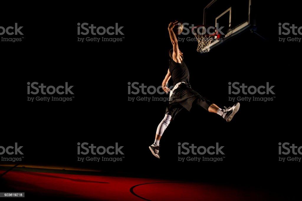 Basketball player makes slam dunk - Man Dunking stock photo