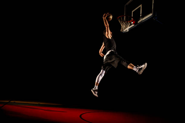 Basketball player makes slam dunk - Man Dunking Basketball player makes slam dunk - Man Dunking slam dunk stock pictures, royalty-free photos & images