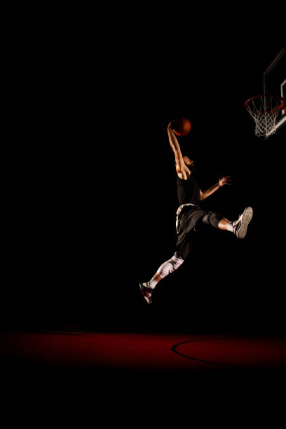 Basketball player makes slam dunk - Man Dunking Basketball player makes slam dunk - Man Dunking jump shot stock pictures, royalty-free photos & images