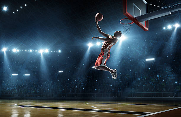 Basketball player makes slam dunk Close up image of professional basketball player about to do slam dunk during basketball game in floodlight basketball court slam dunk stock pictures, royalty-free photos & images