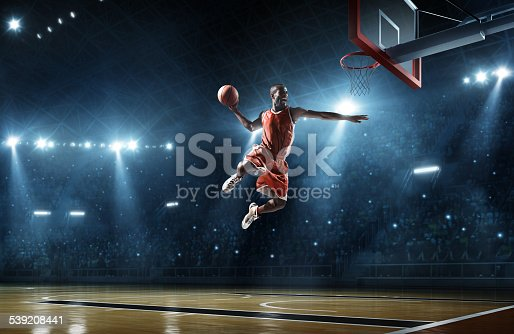 Close up image of professional basketball player about to do slam dunk during basketball game in floodlight basketball court