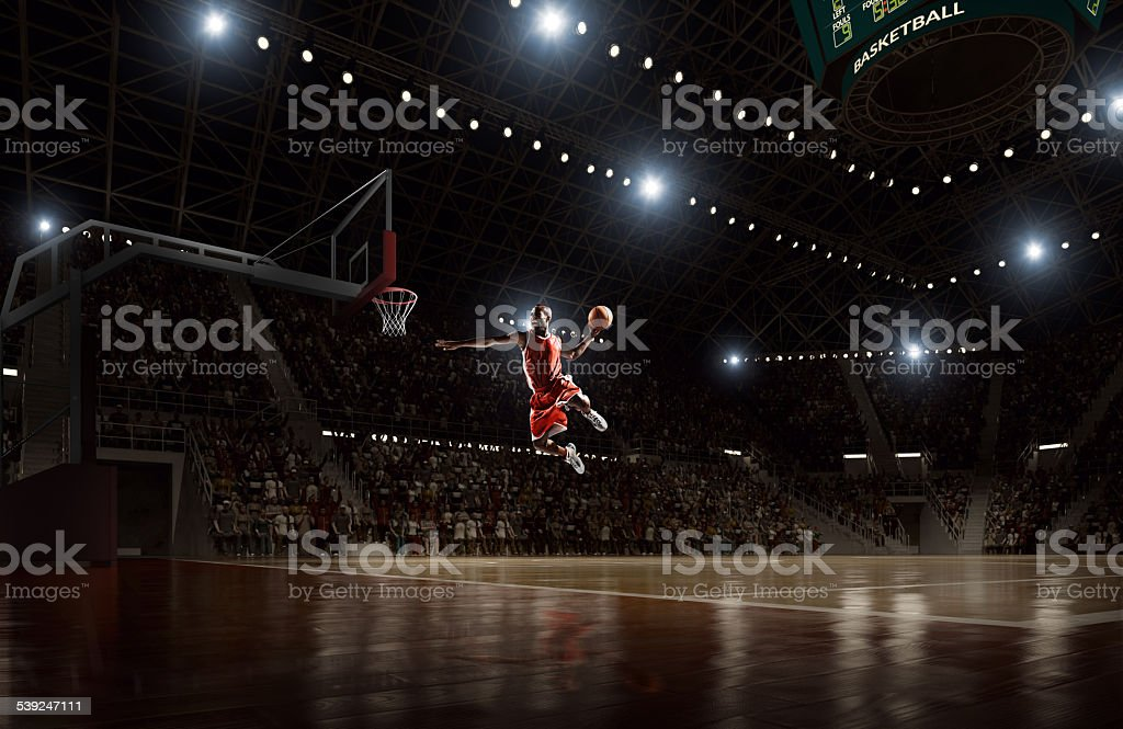 Basketball player makes slam dunk stock photo