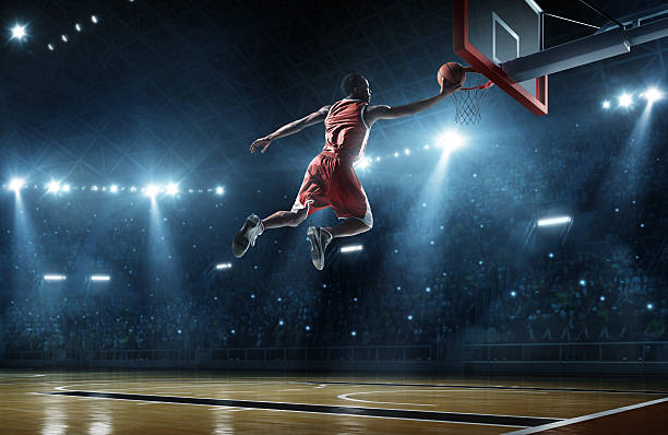 Basketball player making a slam dunk with fans watching Close up image of professional basketball player about to do slam dunk during basketball game in floodlight basketball court jump shot stock pictures, royalty-free photos & images