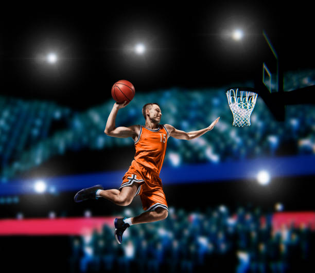 basketball player making slam dunk on basketball arena basketball player making slam dunk on basketball arena lights background slam dunk stock pictures, royalty-free photos & images