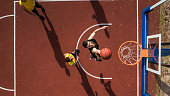 Basketball player scoring with slam dunk, drone point of view, outdoor