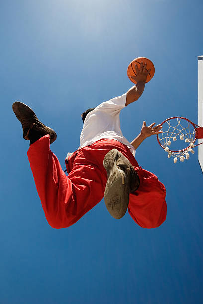 Basketball player A low angle view of a young man aiming at a basketball hoop. jump shot stock pictures, royalty-free photos & images