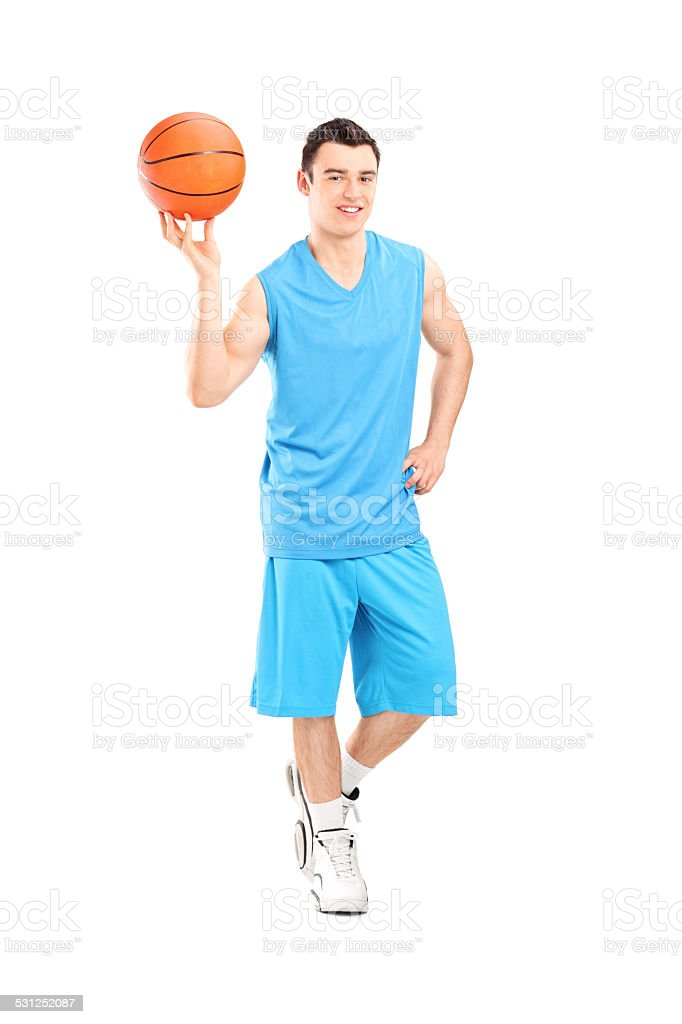 Full length portrait of a basketball player posing with a ball...