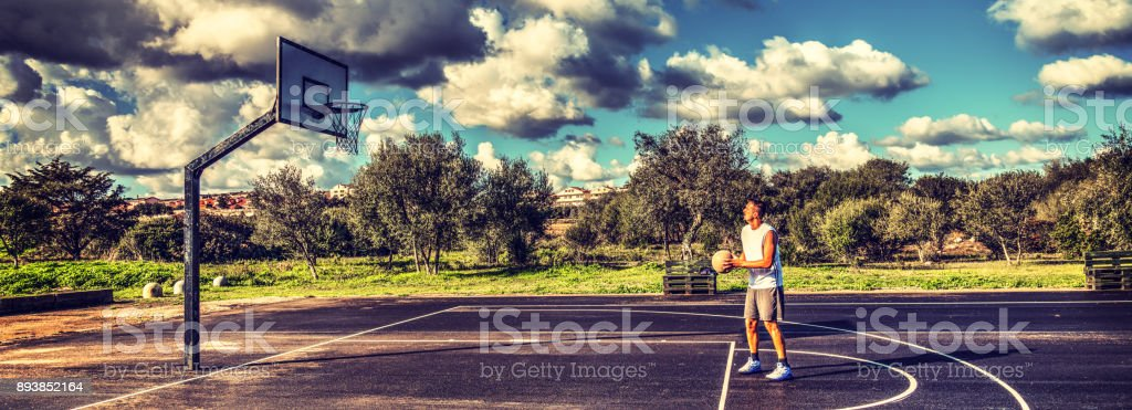 Basketball player practicing free throws in a playground stock photo