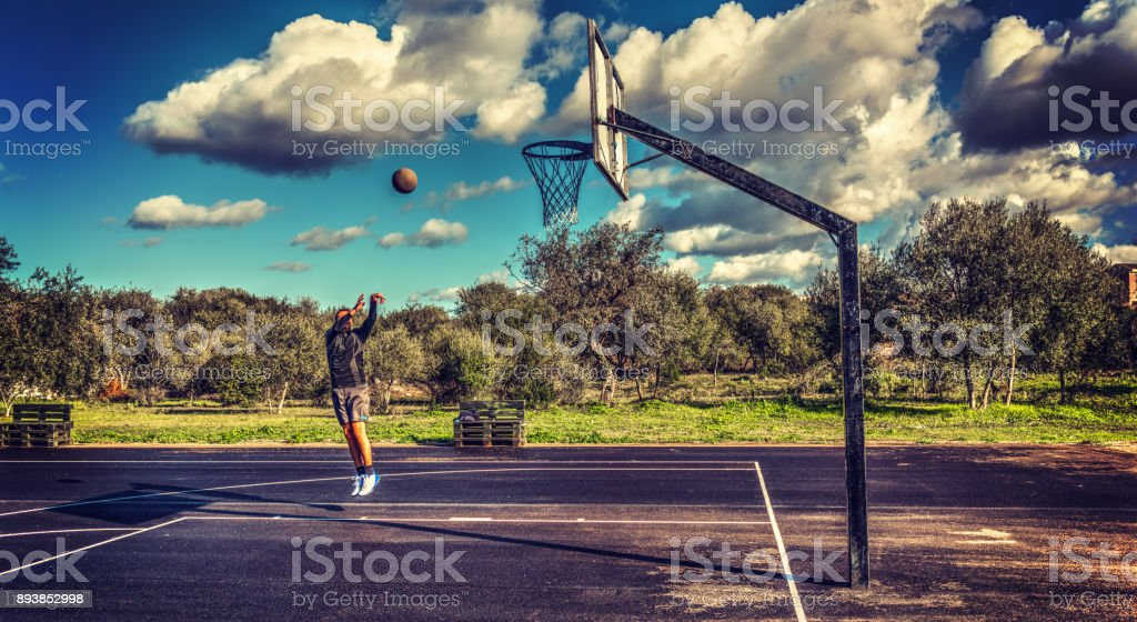 Basketball player practicing jump shot in a picturesque playgropund stock photo