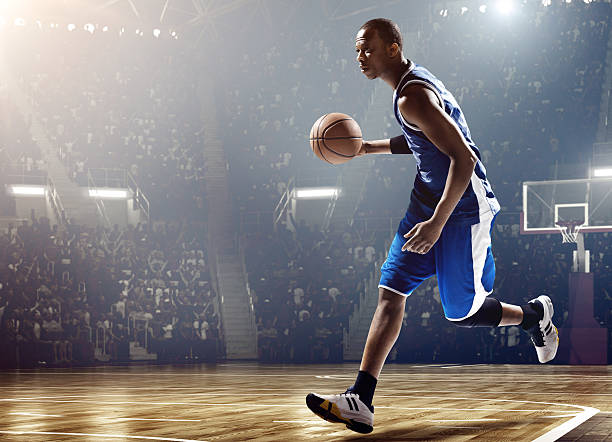 Basketball player running with ball in stadium Low angle view of a professional basketball game. A player is running with a ball. A game is in a indoor floodlit basketball arena. All players are wearing generic unbranded basketball uniform. jump shot stock pictures, royalty-free photos & images