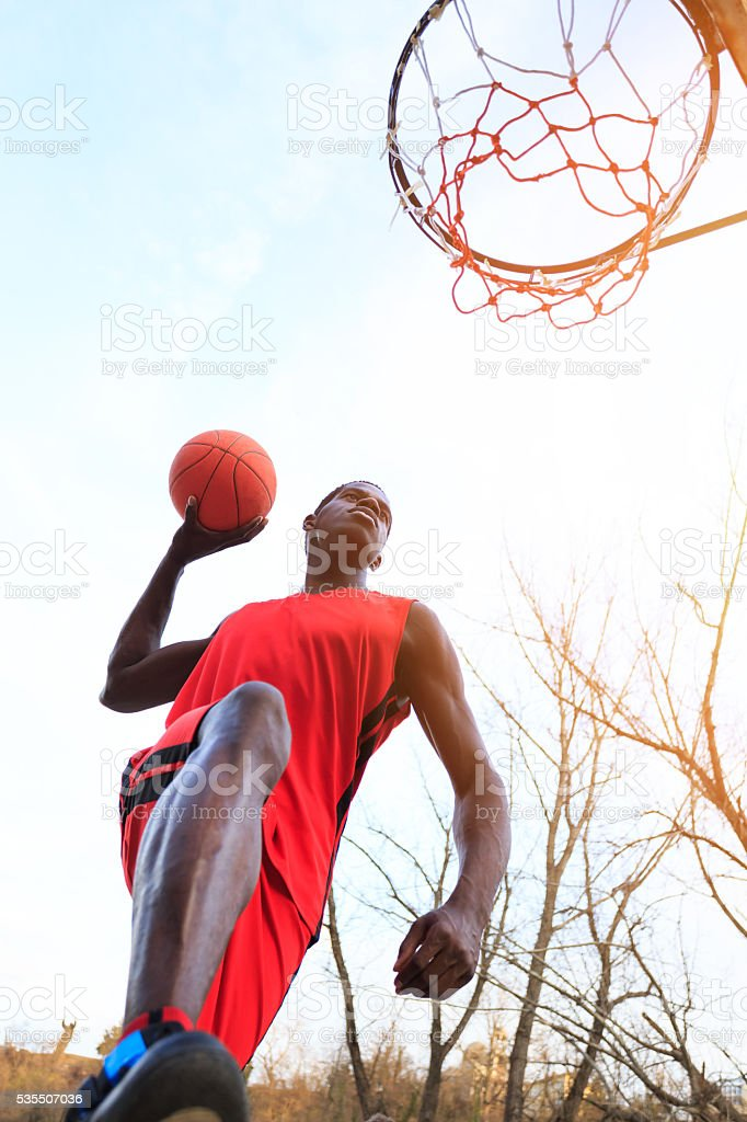 Basketball player scoring slam dunk stock photo