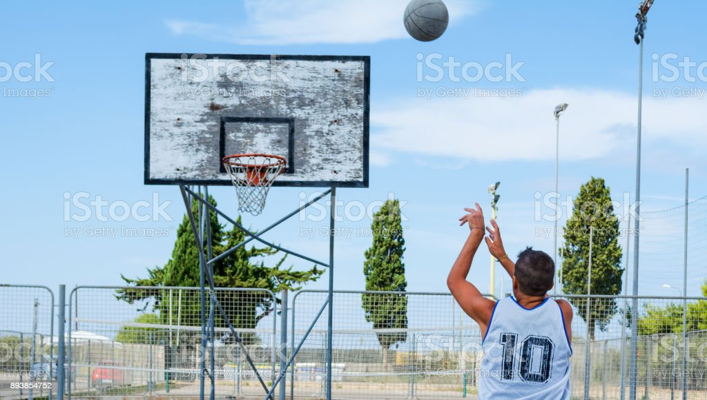 Basketball player shooting in a playground stock photo