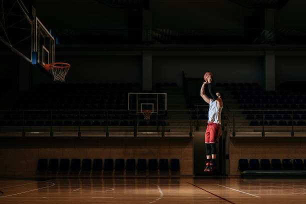 Basketball Player Shooting Basketball player standing alone on indoor court and shooting a ball. jump shot stock pictures, royalty-free photos & images