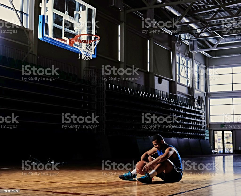 Black professional basketball player sits on a field under the hoop...