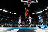 istock Basketball player slam dunking ball 1254565557