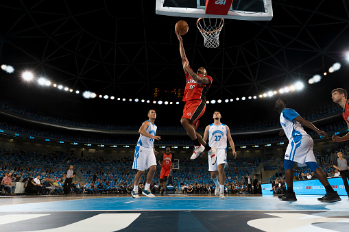 Basketball player in red jersey slam dunking ball during the match.