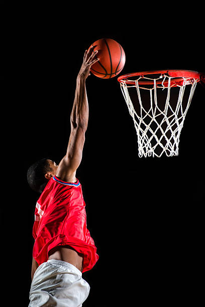 Basketball player slam dunking the ball. Young African-American basketball player is jumping and placing the ball in the hoop.    slam dunk stock pictures, royalty-free photos & images