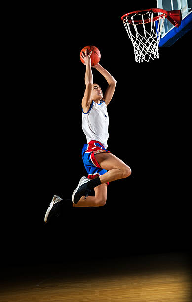 Basketball player slam dunking the ball. Young basketball player is jumping and placing the ball in the hoop. Isolated on black.   http://dl.dropbox.com/u/40117171/sport.jpg jump shot stock pictures, royalty-free photos & images