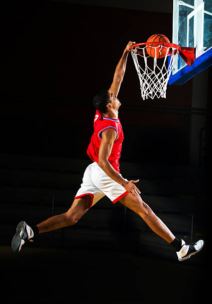 Basketball player slam dunking the ball. Young African American basketball player is jumping and placing the ball in the hoop.   slam dunk stock pictures, royalty-free photos & images