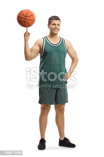 Full length portrait of a basketball player standing and spinning a ball on a finger isolated on white background