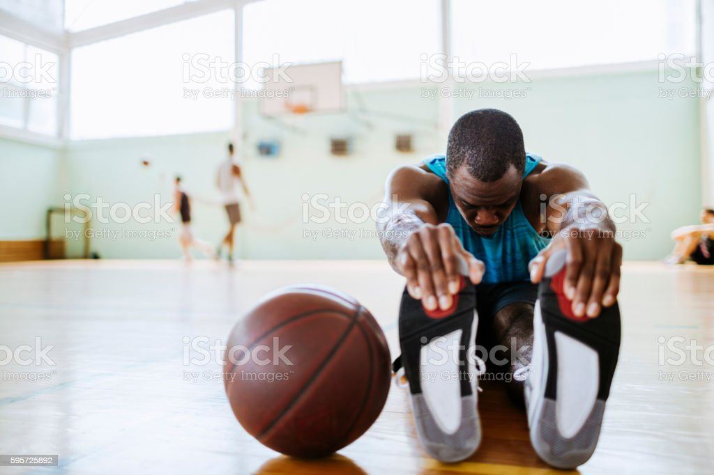 Basketball player stretching stock photo