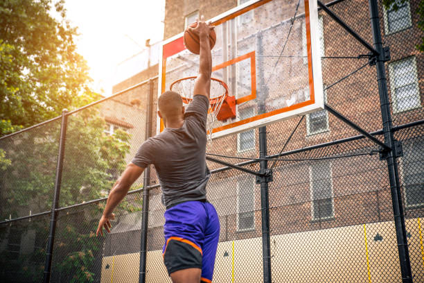 Basketball player training outdoors Afro-american basketball player training on a court in New York - Sportive man playing basket outdoors slam dunk stock pictures, royalty-free photos & images