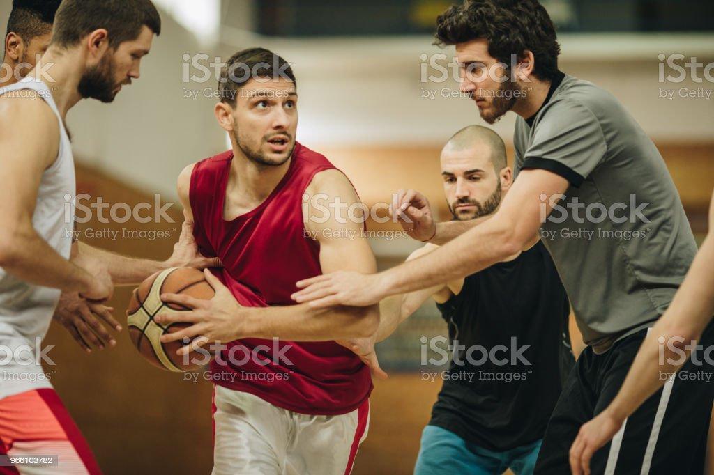 Basketbalspeler probeert te krijgen door defensieve spelers op een wedstrijd. - Royalty-free Aanvallen - Sporten Stockfoto