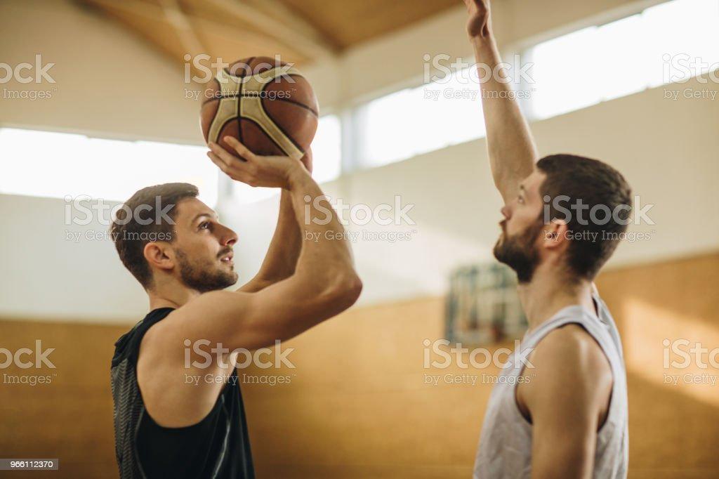 Basketspelare försöker ta ett skott framför försvarspelare. - Royaltyfri Atlet Bildbanksbilder