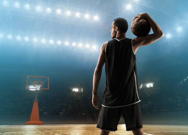 Basketball player with a ball on a floodlit basketball court. View from back Young muscular african american basketball player with a ball on a floodlit basketball court. Sports stadium. jump shot stock pictures, royalty-free photos & images