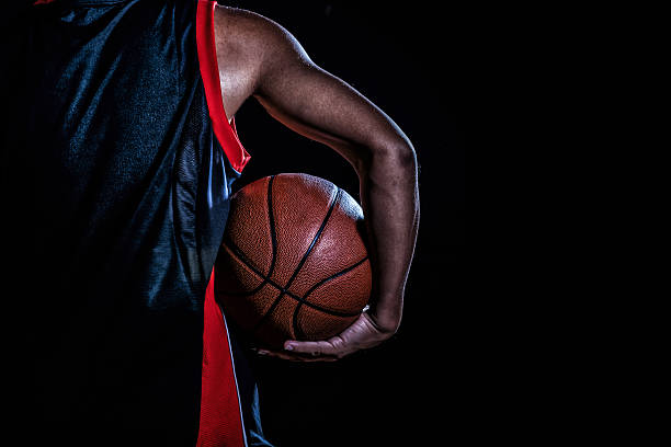 basketball player with a ball on dark background - バスケットボール ストックフォトと画像