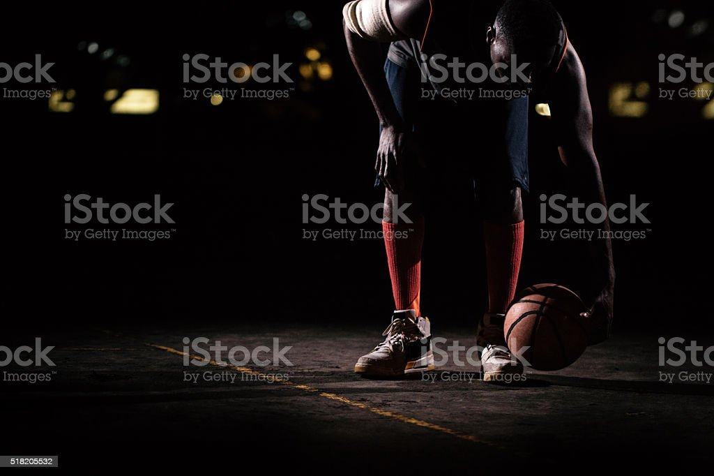 Basketball Players Bending to pick up ball, court ground stock photo