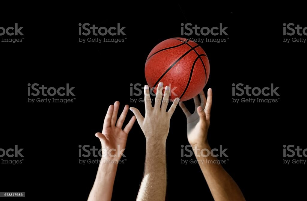 Basketball players hand reaching for the ball in a competition stock photo