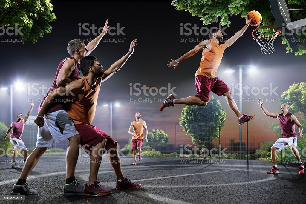 Basketball players in action on court stock photo